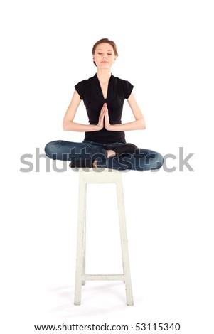 Slim woman sitting on high stool doing yoga meditation technique isolated on white background