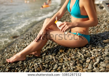 Slim woman tanned lower body in shape lying on pebble beach near sea waves and surf with sunblock cream bottle. Girl applies water resistant sunscreen lotion on legs relaxing in sun holiday. #1081287152