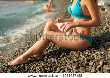 Slim woman tanned lower body in shape lying on pebble beach near sea waves and surf with sunblock cream bottle. Girl applies water resistant sunscreen lotion on legs relaxing in sun holiday. #1081287155