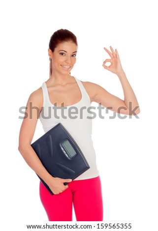 Slim woman with a scale in his arms saying Ok isolated on a white background