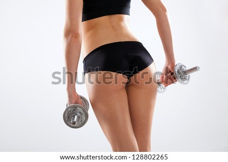 Slim woman with dumbbells, white background