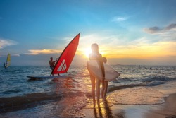 slim woman with family group father, sister are enjoy around with water sports such surfboard, windsurf, kitesurf in the sea beach at sunset scenery