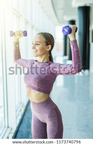 Slim young beautiful girl warming up with weights in health club.