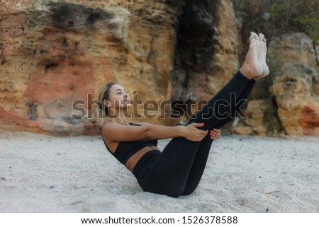 Slim young fit woman doing double twists for abs on the sand on a wild beach. Outdoor training concept. Healthy lifestyle