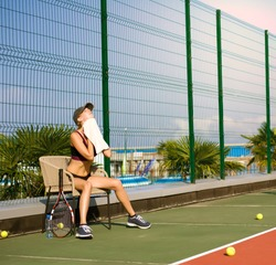 Slim young girl athlete tennis player is on the open tennis court in summer. Wipes up sweat with a towel after a game and sits on a chair.