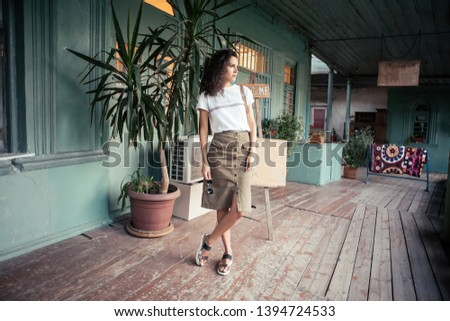 Slim young girl posing on the veranda of an open cafe. Concept of beautiful photos for social networks and resting in famous places #1394724533