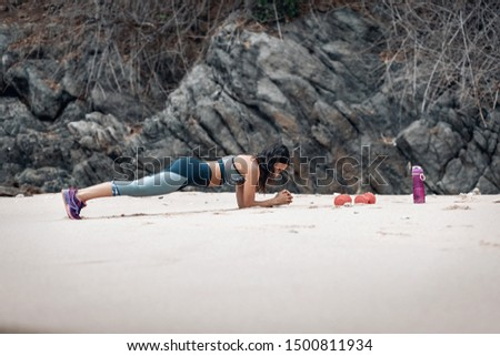 Slim young lady doing plank on the sandy beach, two dumb-bells and a fitness bottle by her side.