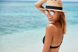 Slim young woman in trendy shades and hat poses on coastline against blue water, has charming smile on face, being satisfied with good summer resort. Lovely fit female tourist on sandy beach alone