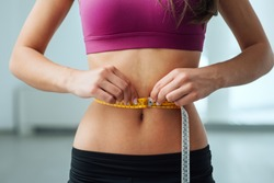 Slim young woman measuring her thin waist with a tape measure, close up