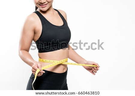 Slim young woman measuring her waist with a measure tape. Weight loss concept. #660463810