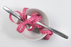slimming health dieting concept - bowl knife and fork cutlery and curved measurement tape peculiar design poster
