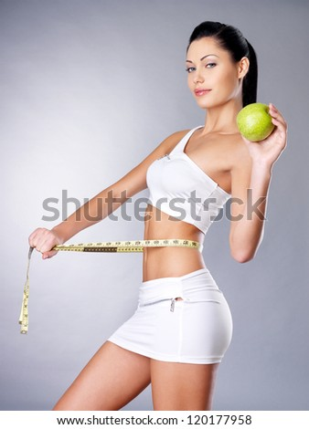 Slimming woman measures figure with a measuring tape and holding the apple.