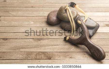 Slingshot Representing the Fight Between David and Goliath on a Wooden Table