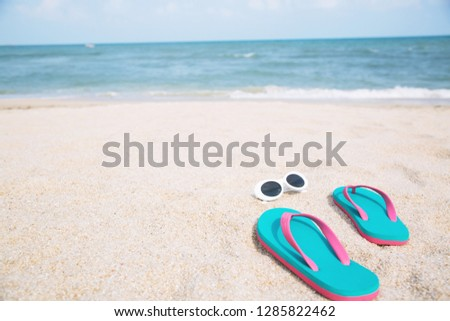 0d4ac6d1c46511 slipper of foot in sandals shoes with sunglasses and Blue ocean wave water  distribution on sandy