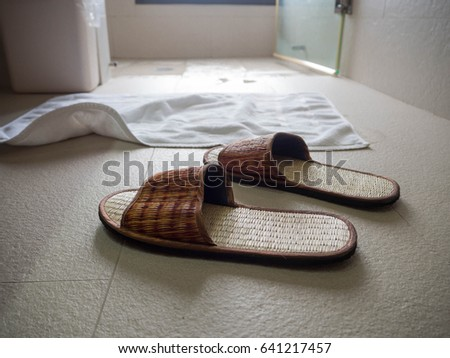 Slippers on the floor in the bathroom the back is a white cloth put in front of the shower #641217457