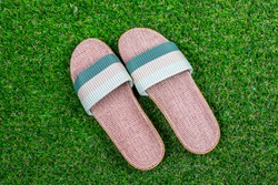 Slippers or sandals on green grass.