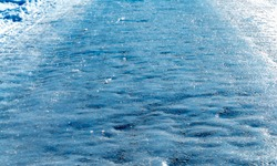 Slippery icy road in the middle of winter. Shallow depth of field.