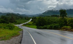 Slippery road / wet road curve to the mountain after rain with rain clouds cover
