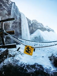 Slippery sign in front of a big waterfall during winter. Everything is wet and icy next to Seljalandsfoss, Iceland