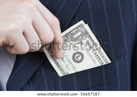 Slipping Money into Pocket closeup of businessman slips money into suit front pocket