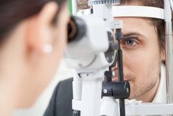 Slit Lamp eye control with the Ophthalmologist / handsome man during a contact lenses examining/ the oculist in eyes clinic doing cornea and retina exam diagnostic / high technology concept eyes care