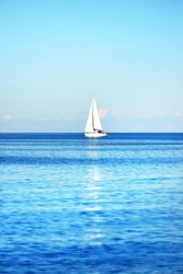 Sloop rigged yacht sailing in a Mediterranean sea on a clear sunny day, Spain. Blue sky with white clouds, reflections on water