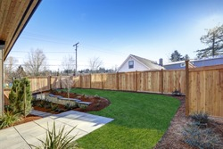 Sloped backyard surrounded by wooden fence. Exterior of New Luxury  home with tiled walkway and green lawn. Northwest, USA