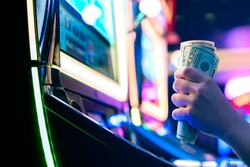 Slot Machine Play Time. Female Gambler Hand hold money bill ready to win the game with one best shot casino close up
