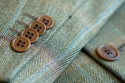 Slotted buttons on the sleeve of a man's jacket as a decorative element of a textile product.Brown buttons with holes sewn in a row.