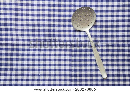 slotted spoon and dish cloth as background.