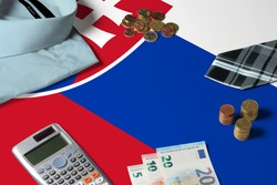 Slovakia flag on minimal money concept table. Coins and financial objects on flag surface. National economy theme.
