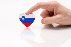 Slovenia flag. Love and respect Slovenia. A man's hand holds a heart in the shape of the Slovenia flag on a white glass surface. The concept of patriotism and pride.