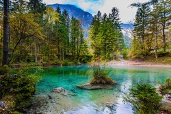 Slovenia, Julian Alps. Picturesque shallow lake with glacial greenish water. Light fog rises above the water. Autumn forest in a mountain valley