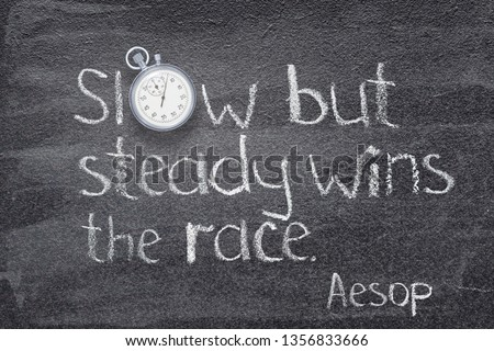 Photo of  Slow but steady wins the race - quote of ancient Greek story teller Aesop written on chalkboard with stopwatch instead of O