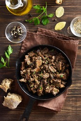 Slow cooked pulled beef in frying pan on wooden background. Top view, flat lay