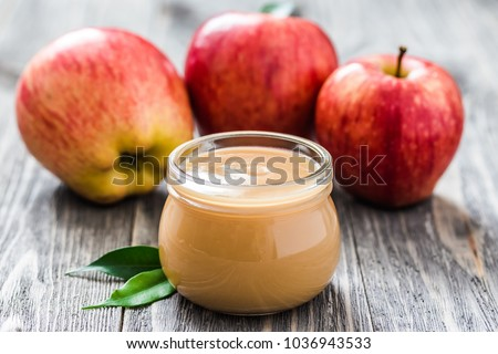 Slow cooker plum applesauce in glass jar and red ripe apples on rustic wooden background. Selective focus, space for text.  stock photo
