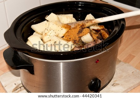 Slow cooker with potatoes and wooden spoon.
