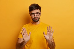 Slow down. Serious looking displeased bearded man shows stop gesture, asks to hold horses, keeps palms towards camera, says take it easy and control your behaviour, stands against yellow background