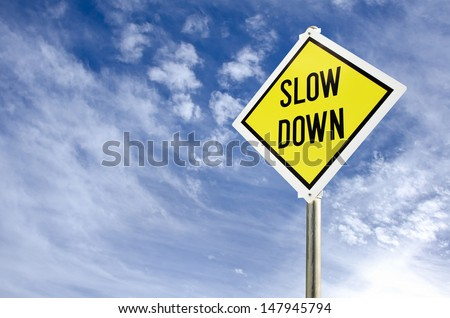 Slow Down yellow road sign on blue sky with clouds background