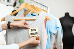 Slow fashion. Clothes on hangers in a shop showcase. Recycled organic apparel.