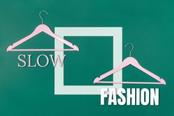 Slow Fashion text and two empty coat hangers on green background. Sustainable approach to manufacturing and eco-friendly anti-consumerism concept. Conscious buying awareness. Copy space