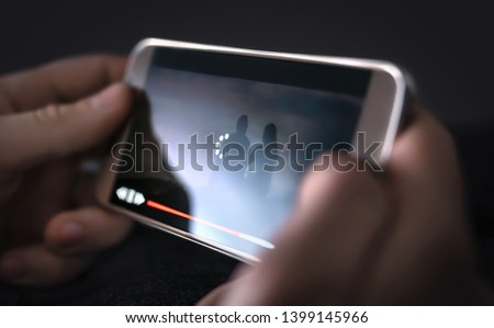 Slow internet, video load and download speed. Watching movie online. Loading icon on screen. Frustrated angry person with poor and bad broadcast connection for entertainment. Man with mobile phone.