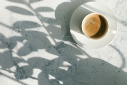 Slow living, cup of coffee in the morning light, sunlight shadow, morning breakfast concept, top view, copy space