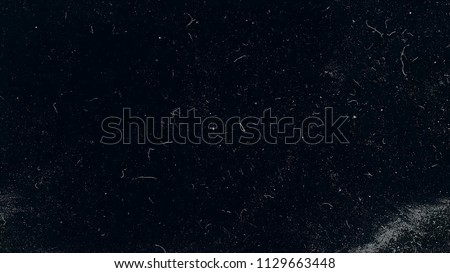 Slow motion macro shot of dust particles over black background. White dust particles moving slowly in space on black background. Abstract particle moving background. Slow motion macro dust particles