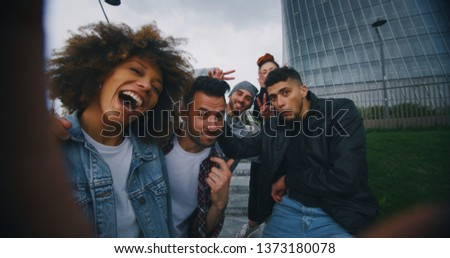 Slow motion of group of young friends of different ethnicities are having fun and making a selfie together with cellular phone in a city center with skyscrapers.