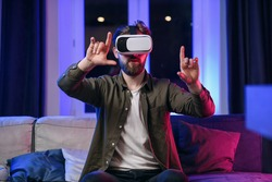 Slow motion of likable cheerful positive man with beard which working on the imaginary touchscreen in augmented reality goggles