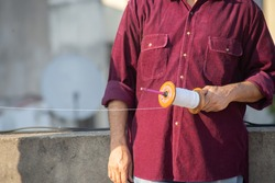 Slow motion shot of man holding a charki phirki thread spool in the crook of his elbow and winding it with the other hand to ensure taughtness for the famed kite fighting festival of makar sankranti