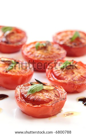 Slow-roasted vine tomatoes, with balsamic, olive oil, garlic and basil.  Focus on front tomato.