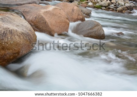 Slow shutter speed image of small waterfall from the gap between rock in the river