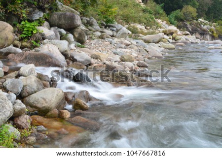 Slow shutter speed image of small waterfall from the gap between rock in the river (soft focus)